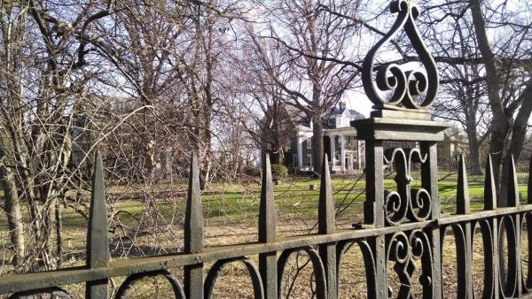 Mansion through gate and trees